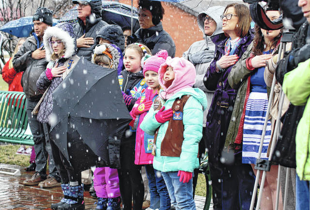 Barb Slone | Greene County News Girl Scouts and families say the Pledge of Allegiance during the 60th anniversary memorial service at Angels' Pass Memorial March 17 in Beavercreek Community Park. On March 18, 1959, eight Girl Scouts and two leaders from Troop 133 were returning from working on a badge at the Xenia Library when their vehicle was struck by a train while crossing the Factory Road tracks. No one survived.