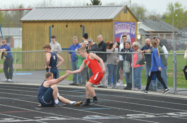 Cedarville's Jared Waltz helps a runner from Germantown Valley View back onto his feat after the Spartan took a tumble at the finish line during the boys 100-meter race at a recent Greeneview HS Quad meet, in Jamestown.