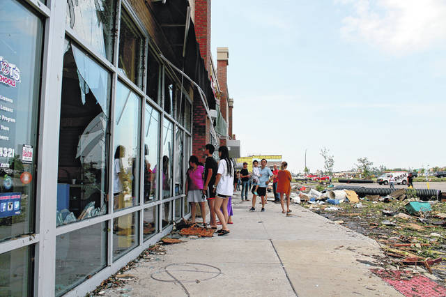 Anna Bolton | Greene County News People look through the shattered window of a business May 28 near North Fairfield Road in Beavercreek.