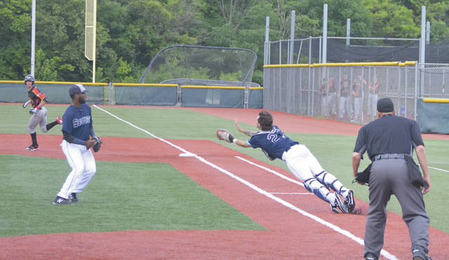 Xenia Scouts catcher Allan Goodwin makes a diving try at a towering fly ball that started out in foul territory, then blew back into play. Goodwin lost control of the catch as he hit the ground. Visiting Hamilton went on to defeat Xenia, 7-3, June 7 at the Athletes In Action Sports Complex' Grady's Field.