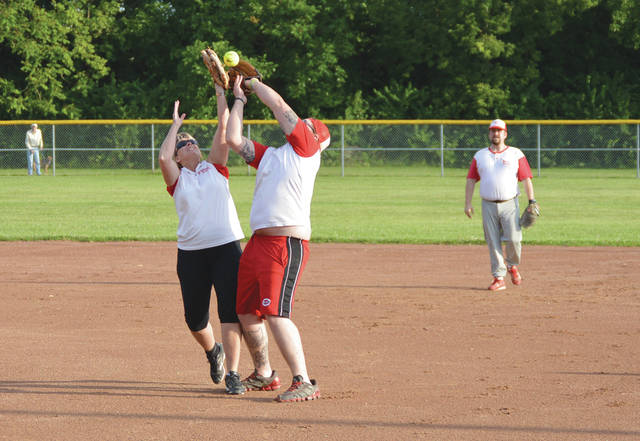 This pair of St. Mark's Episcopal church league softball players collided on this infield fly ball, and still managed to make the catch, Thursday evening at Fairfield Park in Fairborn.