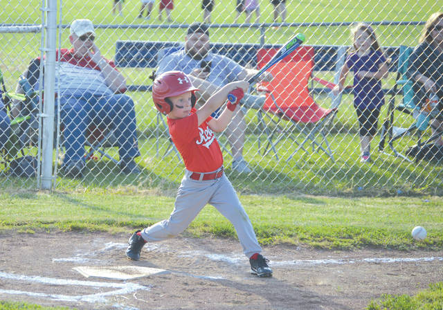 A member of the Remax The Blakely Bunch Reds smacks a ground-ball single into right field, Tuesday June 11 in Fairborn Little League 7-8 year-olds baseball action.
