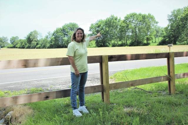 Linda Collins   Greene County News Kassie Lester who is standing at the entrance to Pearl's Fen and pointing to the tree-lined land that is the proposed site of the biosolids storage ponds. These open-top ponds will have the capacity of storing a combined total of 32 million gallons of biosolids. Pearl Fen is located on the west side of Byron Road. The proposed site for the two biosolids storage ponds is located directly across the road on the east side of Byron.