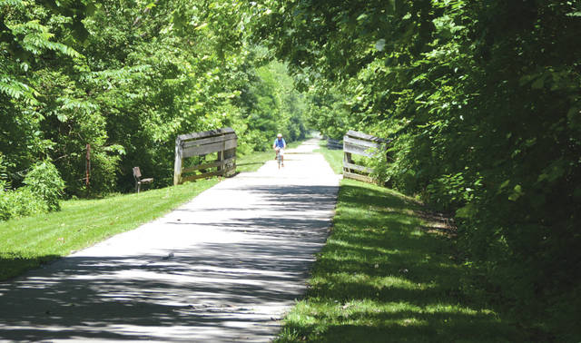 A bicyclist heads east along the Creekside Trail just west of the Kil-Kare Raceway grounds in Xenia Township.