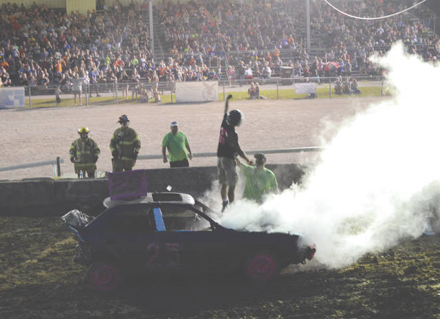 Brandon Pinkerton of New Vienna celebrates with the Greene County Fairgrounds crowd after winning the first heat of the Street Stock Compact division, Monday July 29 during the annual Smash It demolition derby in Xenia.