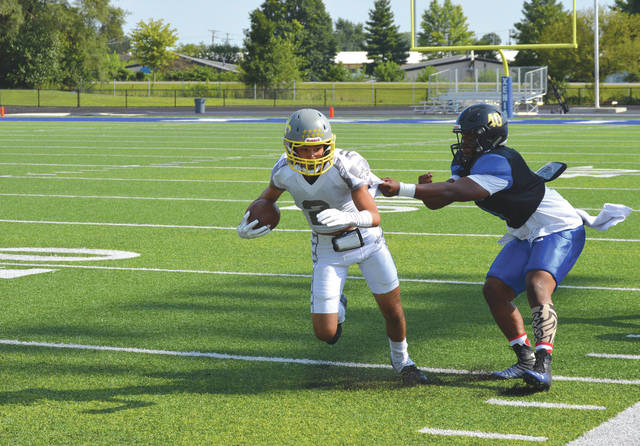 Everett Harding Jr. of the Ohio Valley Saints tries to spin out of the grasp of Jordan Masterson of the West Virginia Storm, during Saturday's Premier Amateur Football League game at Doug Adams Stadium in Xenia.
