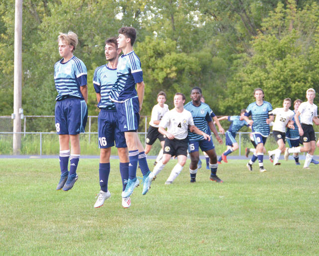 Fairborn's Donnie Lynn, Elijah Picarello and Josh Best leap to try and block a Sidney free kick near the Skyhawks goal, during the first half of a Miami Valley League boys soccer match in Fairborn.