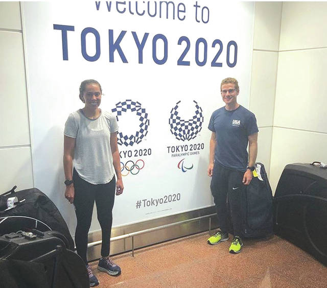 Cedarville University distance runner Grace Norman (left) and a Team USA teammate pose in front of a Tokyo airport banner celebrating the Tokyo 2020 Olympic and Paralympic Games. Norman and several other members of the U.S. national team arrived Aug. 10 in Tokyo to compete in an international test event of the triathlon and paratriathlon race layouts.