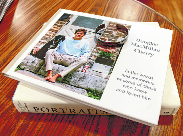 Anna Bolton | Greene County News Every day, Barbara Cherry Mills wears a bracelet bearing the name of her brother, Doug Cherry, who died on Sept. 11, 2001 in the World Trade Center. She also holds onto a memorial photo book she and her sister Meg and mother Anne created together.