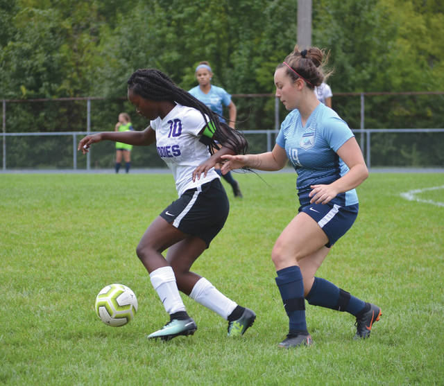 Fairborn sophomore defender Jocelyn Gale (19) and a Middletown player chase after the ball, during Saturday's girls varsity soccer match at Fairborn High School.