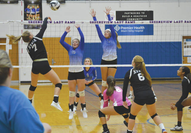 Greeneview's Sadie Trisel (10) and Sarah Trisel (11) go up for a block try against Xenia's Jaca McAvene, during Wednesday's girls varsity volleyball match in Jamestown.