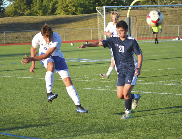 Xenia's Neko Dykman (3) launches a kick downfield as Legacy Christian's Kevin McEntyre closes in, during a boys varsity high school soccer match Saturday at the Athletes In Action Sports Complex.