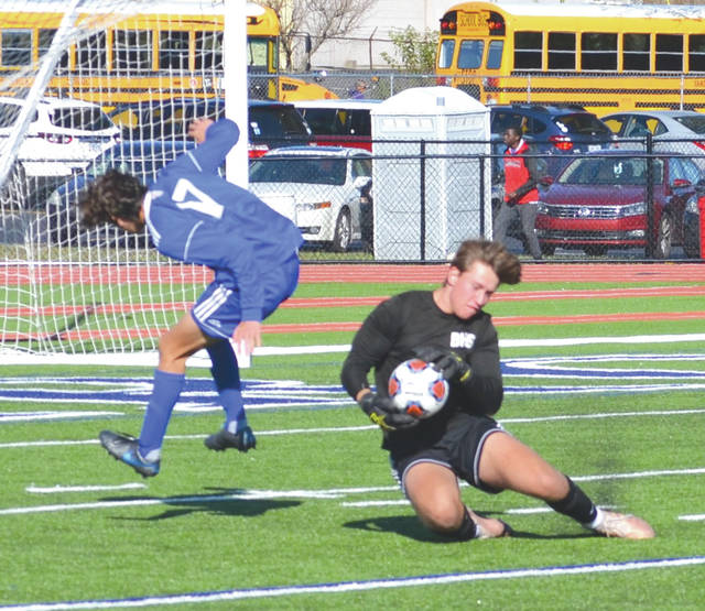 Ben Del Cid (17) of Carroll leaps over the Vandalia Butler goalkeeper during Saturday's regular season match at Spoerl-Bartlett Field in Riverside.