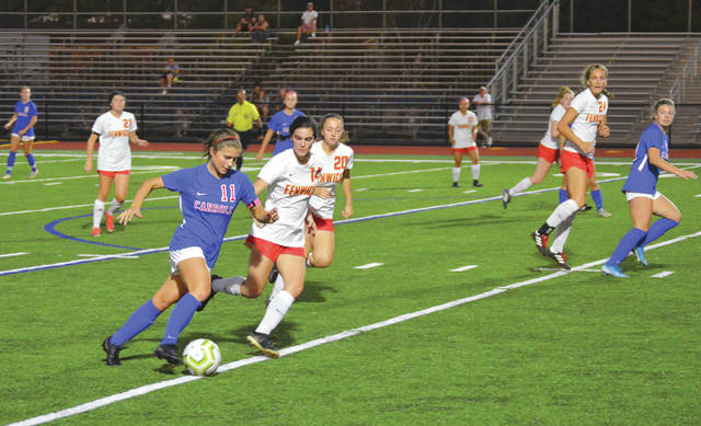Carroll senior midfielder Alaina Casey (11) drives up field as Fenwick junior defender Lizzie Webster (14) closes in, during first-half action in a girls varsity soccer match Wednesday night, Oct. 2at Spoerl-Bartlett Field in Riverside.