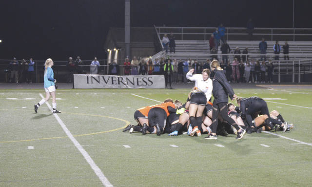 The Beavercreek girls soccer team piles onto Cassie Rodriguez, after the junior forward clinched the win with a penalty kick goal, Thursday at Bellbrook High School.