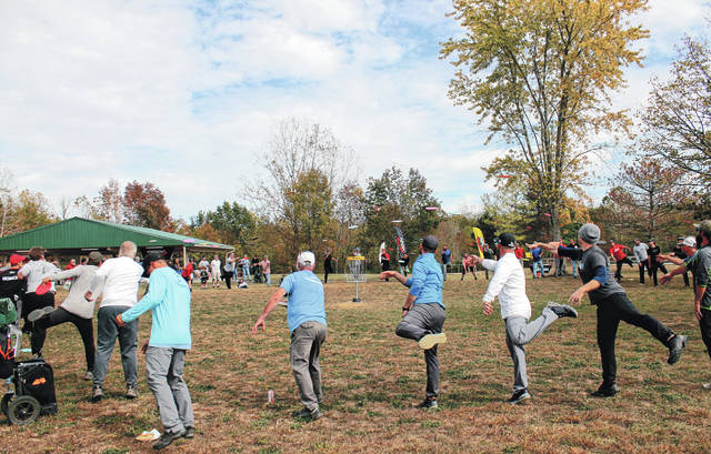 A group of disc golf players throw discs into a basket Oct. 16 before the dedication ofGreene County Parks & Trails' Caesar Ford Park Disc Golf Course.