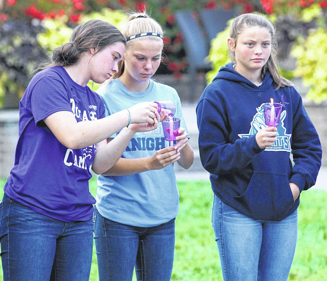 File photo Students participate in a candle lighting ceremony at the 2018 Pause for Peace vigil.