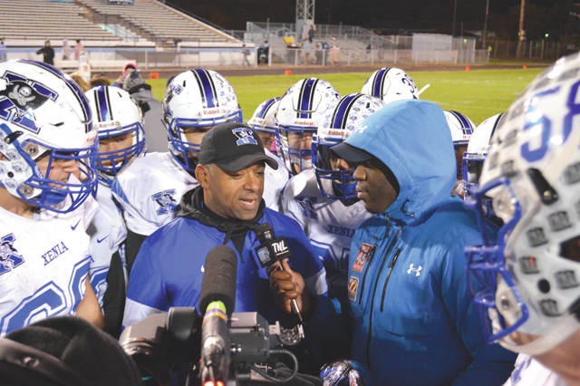 The Xenia team gathers around coach Trace Smitherman as he talks with ABC22 and Fox45 after Thursday's high school football game win at Fairborn's Memorial Stadium.