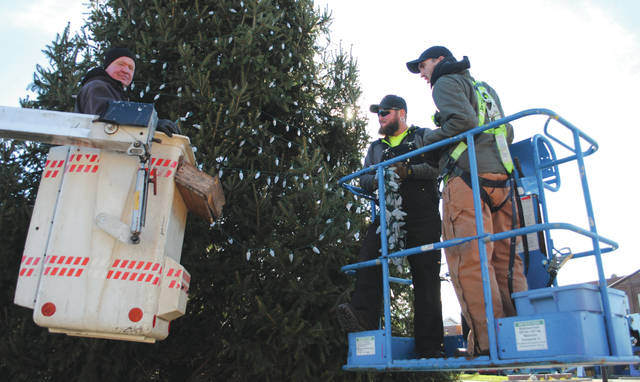 File photos The City of Fairborn is seeking a donated tree by one of its citizens to illuminate the Hometown Holiday Parade and Christmas Tree Lighting slated for Friday, Dec. 6. Pictured are city employees adorning a previous tree with lights ahead of the annual event.
