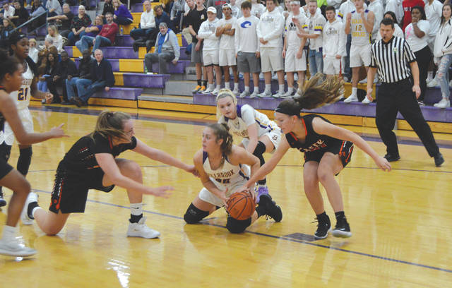 Bellbrook's Kayla Paul (30) looks for an open teammate as Beavercreek's Anna Landing (left) and Riley Ryan (right) try to swipe the ball away from her, during the first half of Friday's Nov. 22 season opening girls high school basketball game at Bellbrook High School.