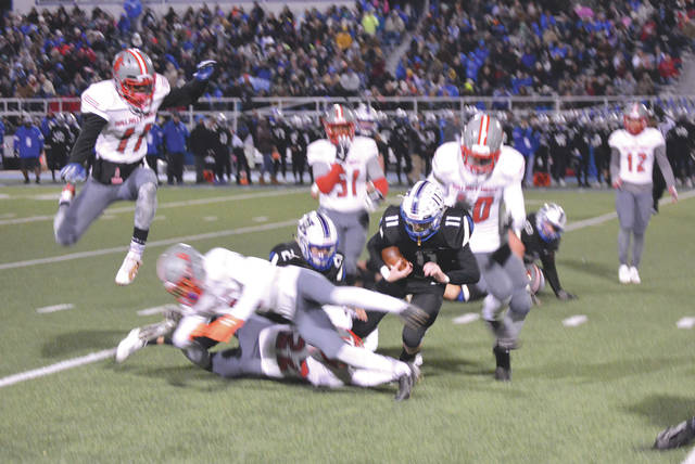 Xenia quarterback Brett Russell (11) is brought down by a Walnut Ridge tackler during the first half of Friday's Division II Regional Quarterfinal high school football playoff game, Nov. 8 at Doug Adams Stadium.