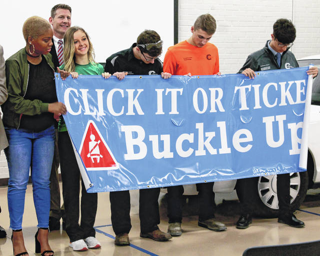Greene County Career Center students Treazure Lee, Logan Pier, Tye Bennett, Lane Hilderbrand and Alla'Eldeen Idrees unroll the Click it or Ticket sign during the presentation.