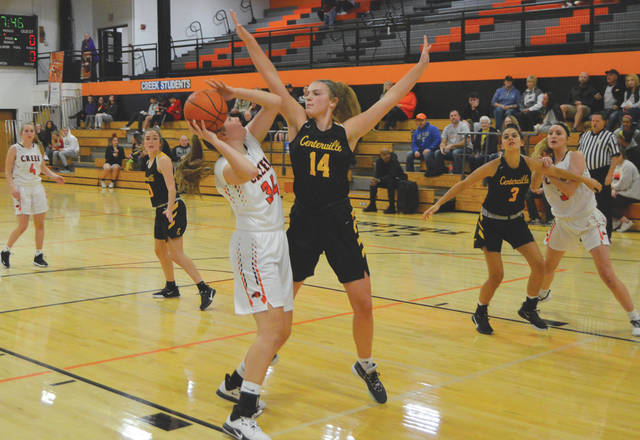 Centerville post player Molly Scott (14) contests an inside shot by Beavercreek's Anna Landing, during the first half of Monday's girls high school varsity basketball game on the Ed Zink Fieldhouse floor, in Beavercreek.
