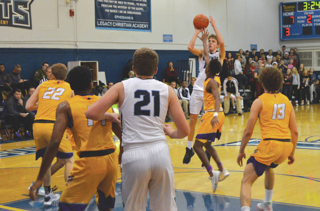 Jonathan Riddle puts up a jumper over a crowd of Emmanuel Christian Lions, during the first half of Friday's Dec. 13 boys high school basketball game at Legacy Christian Academy, in Xenia. Riddle scored a game-high 19 points in a 47-42 home loss.
