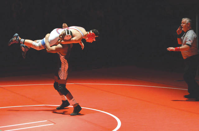 Xenia 132-pounder Desmond Diggs lifts Carroll's Elija Eagy during the first round of their match, Friday, Jan. 31 at Carroll High.