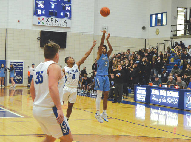 Fairborn junior guard Dwight Lewis (3) puts up a three-point shot as Xenia's Dylan Hoosier closes in to defend, Friday Jan. 10 at Xenia High School.