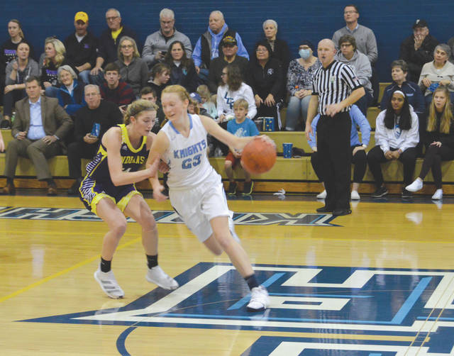 With the crowd looking on, Legacy Christian's Emma Hess (23) dribbles away from Mechanicsburg standout Kasey Schipfer, Jan. 23 in the second half in Xenia.