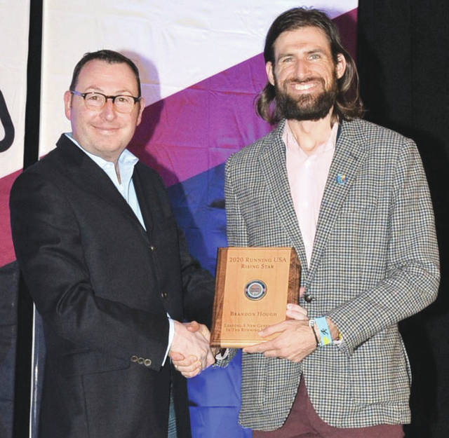 Submitted photo Left to right, CEO of Running USA, Rich Harshbarger, presents Air Force Marathon director, Brandon Hough, the Rising Star award at the Running USA Industry Conference.