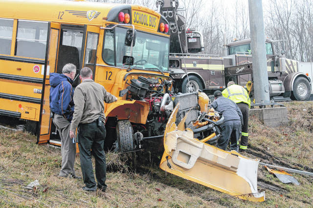 Photos by Anna Bolton | Greene County News Fairborn City Schools Superintendent Gene Lolli, left, looks at the damage of the school bus as it is pulled out of the field after a crash off U.S. Route 35 near Valley Road Tuesday morning.