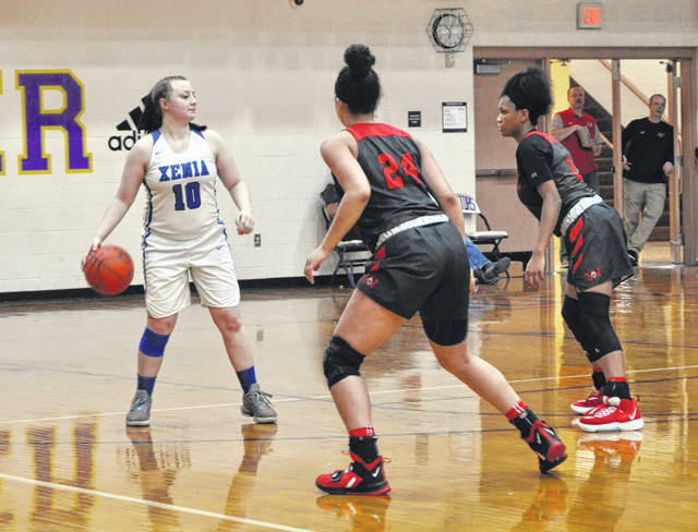 Scott Halasz | Greene County News Xenia's Kamea Baker looks for someone to pass to while being guarded by Wayne's Jaida Wolfork and a teammate.