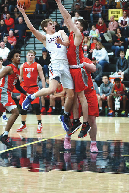 Carroll senior forward Jaden Dahm (2) puts up a hook shot over a Troy defender, Feb. 22 in a 52-35 Patriots win in a Division I sectional first round game at Centerville High School. Dahm led the Patriots with 19 points scored in the win.
