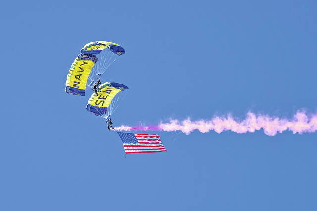 The U.S. Navy parachute demonstration team, the Leap Frogs, carry an American flag during a performance for spectators attending the Centennial of Naval Aviation Open House and Parade of Flight at Naval Air Station North Island. The Navy is observing the Centennial of Naval Aviation with a series of nationwide events celebrating 100 years of heritage, progress and achievement in naval aviation.