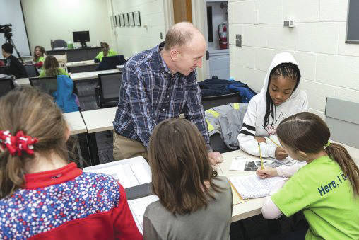 Submitted photo Bill Stolz, archivist for reference and outreach at Wright State, assists Miami Valley School students who conducted research at Special Collections and Archives.