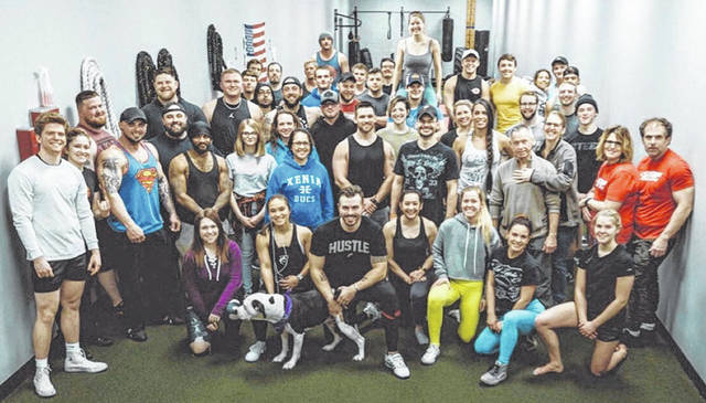 Photo courtesy Kelly Pellettiere Snap Fitness owner Corey Jackowski, holding his dog, poses with most of his members. A gofundme was organized by one member to help him survive while being shut down due to the coronavirus.