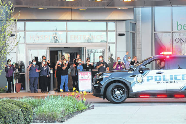 Photos by Anna Bolton | Greene County News Soin Medical Center workers wave as a Beavercreek police cruiser rolls by the hospital entrance April 21.
