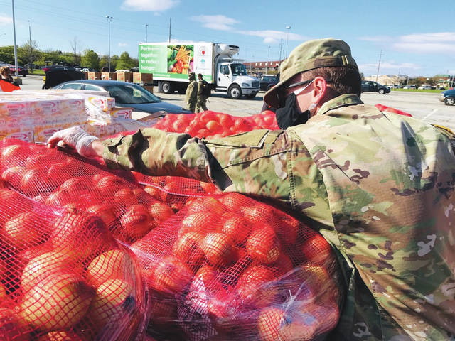 Submitted photo The Foodbank used a no-touch distribution method in loading food into the vehicles' trunks and backseats. The 30 Foodbank volunteers and 29 members of the Ohio National Guard working with the organization wore protective masks and gloves.