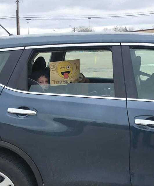"""A student holding a sign out the window that says """"thank you"""" and """"we miss you."""""""