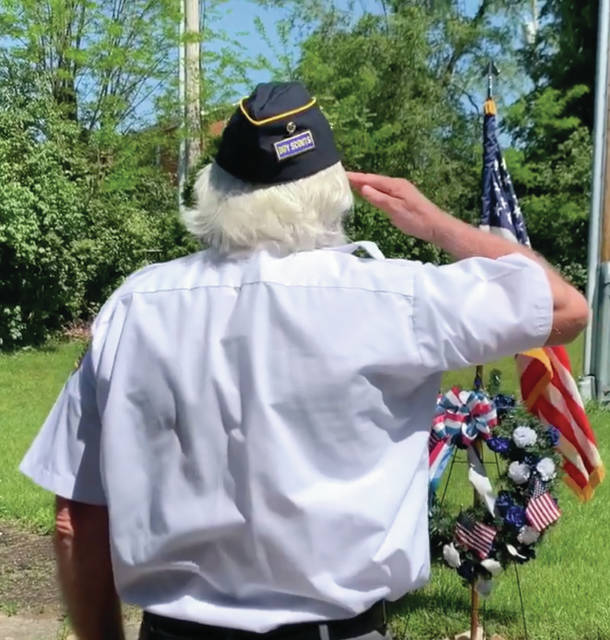 Screenshot of virtual ceremony Fairborn American Legion Post 526 Chaplain Kevin Knapp places a wreath at the American flag May 25 in a token of remembrance of fallen soldiers during the Memorial Day ceremony. The ceremony, traditionally held at Fairfield Cemetery, was instead recorded and shown on TV, Facebook and YouTube for the public to see.