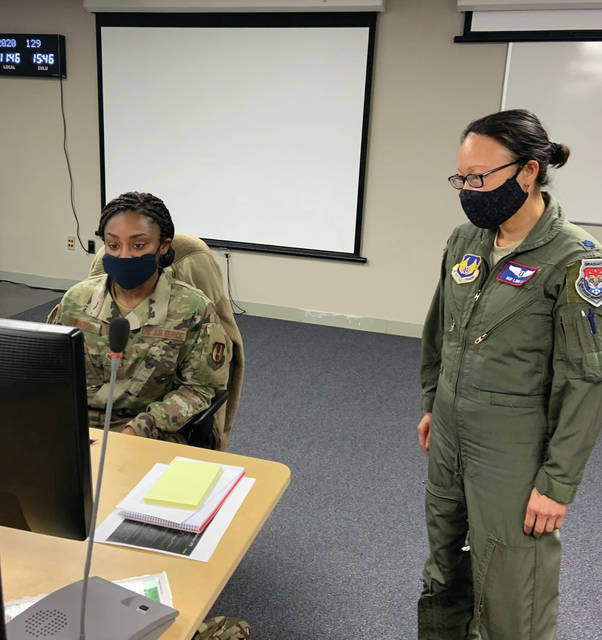 Photo courtesy Stacey Geiger, U.S. Air Force Col. Hui Li, 88th Medical Group's chief of aerospace medicine, 88th Air Base Wing public health emergency officer and Wright-Patt AFB COVID-19 incident commander, talks with ICC administrative support Senior Airman Quaniesha Swinton while working in the incident control center.