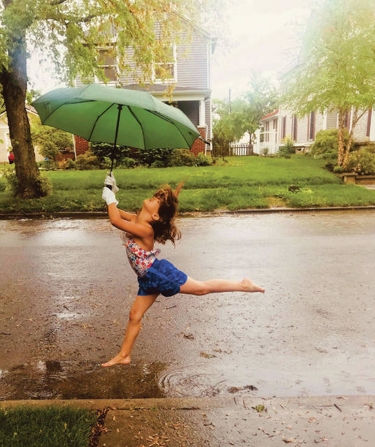 Submitted photo Samantha Coppock, 7, dances in the rain May 18 on Grand Avenue.