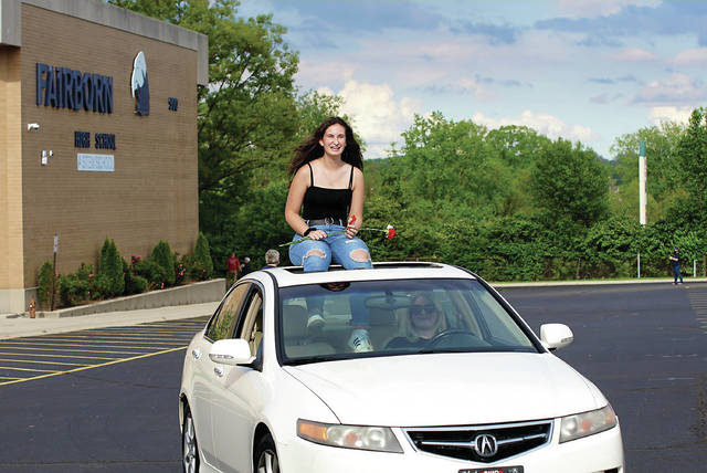 Barb Slone | Greene County News Fairborn High School class of 2020 seniors drove — or rode — around their high school one last time the evening of May 22, what would have been their graduation date if not for the COVID-19 pandemic. Students were met by masked friends, family and staff members who rang cow bells, blew horns and cheered with signs as they circled the school. Each senior received a carnation, just as they would have at the beginning of their final walk.