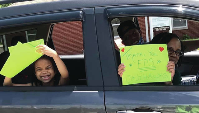 Submitted photos Fairborn Primary School students from Main and Wright campuses drive by in a end-of-the-year parade May 28. Teachers spaced out on the sidewalk six feet apart to hold up signs and wave at the cars for a final celebration.