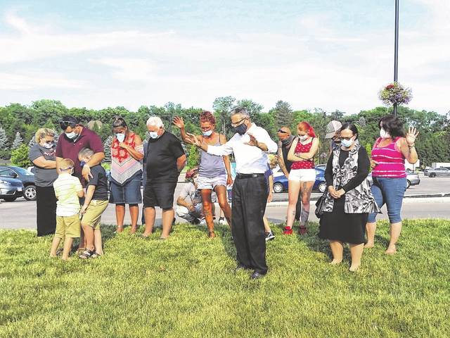London Bishop   Greene County News Family members of Sheila Johnson pray for her and others battling COVID-19 outside Kettering Medical Center on Thursday. Johnson's family said she contracted coronavirus from Gates of Praise Church in early June.