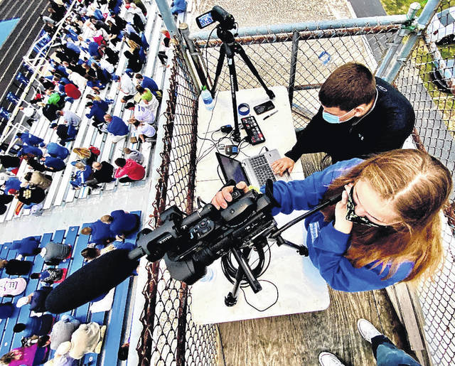 """Junior Gracie Norris ran the camera, while senior Aidan Cowell was in charge of the graphics, which included showing """"touchdown"""" on the screen when Xenia scored."""