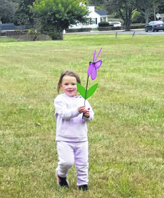 Merrell Hill's great-granddaughter carries a purple flower on Saturday. Purple flowers signify that the bearer has lost a family member to Alzheimer's disease.