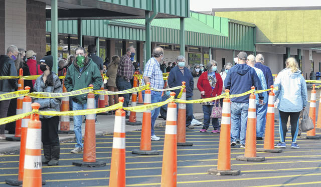 Scott Halasz | Greene County News Early voting began Tuesday in Ohio. The Greene County Board of Elections had long, socially distant lines most of the day. Cones were set up to help indicate where voters should stand while waiting.